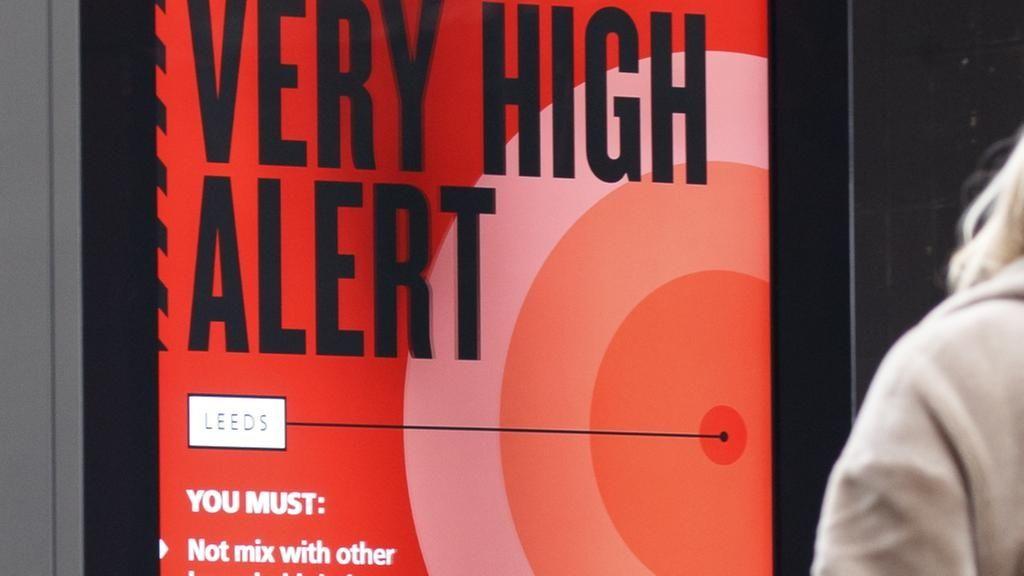 Auf einer Anzeigetafel in London wird vor einem hohen Ansteckungsrisiko mit dem Coronavirus gewarnt.