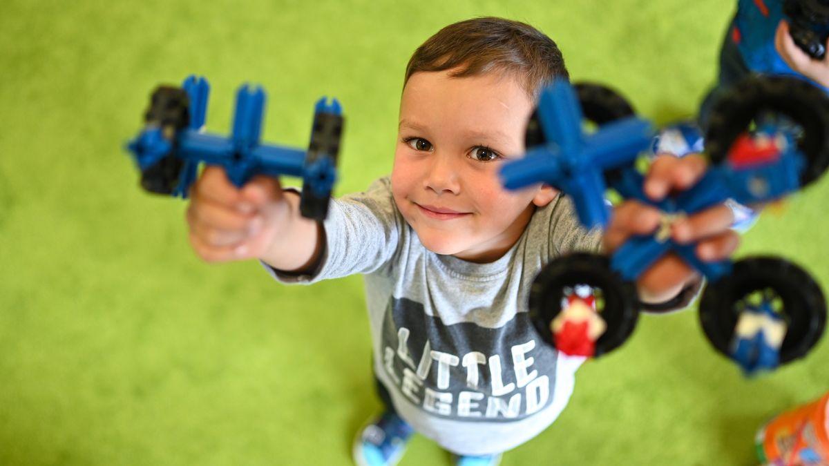 Kind hält Spielzeug in die Kamera