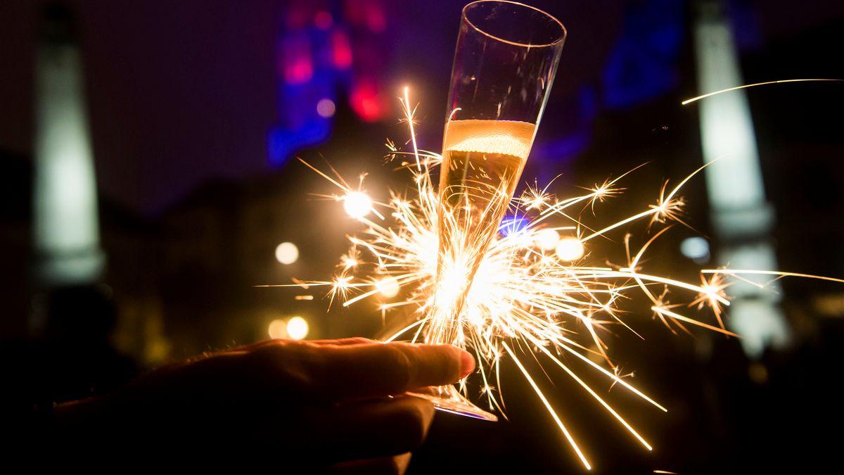 Mit einem Glas Champagner und einer Wunderkerze in der Hand feiert eine Frau den Jahreswechsel (Symbolbild).