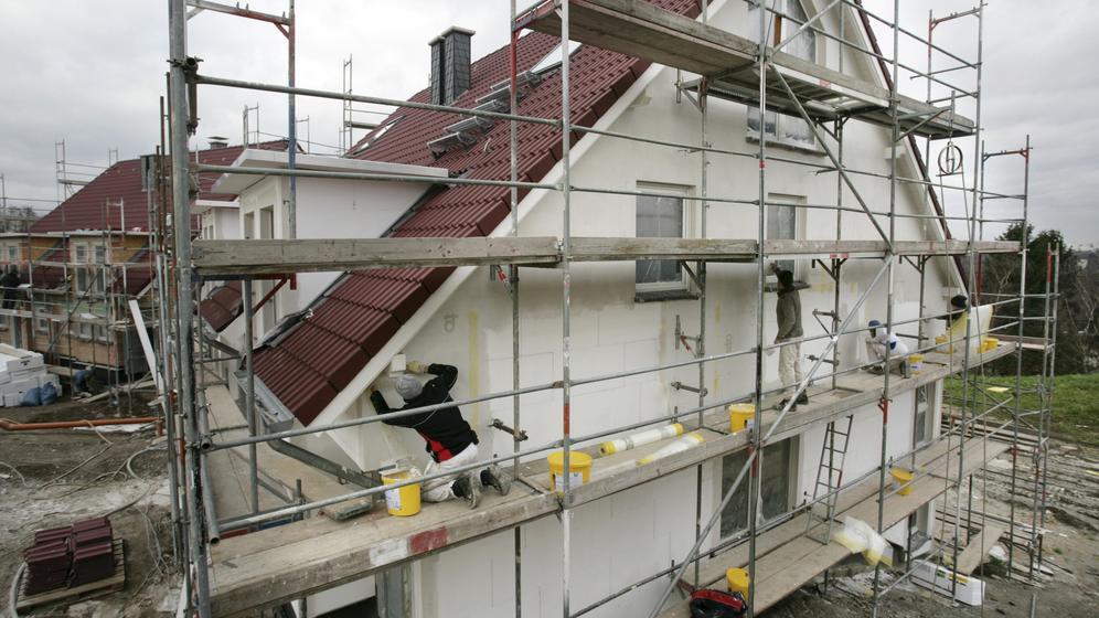 Handwerker isolieren ein Gebäude von außen | Bild:picture alliance/imageBROKER