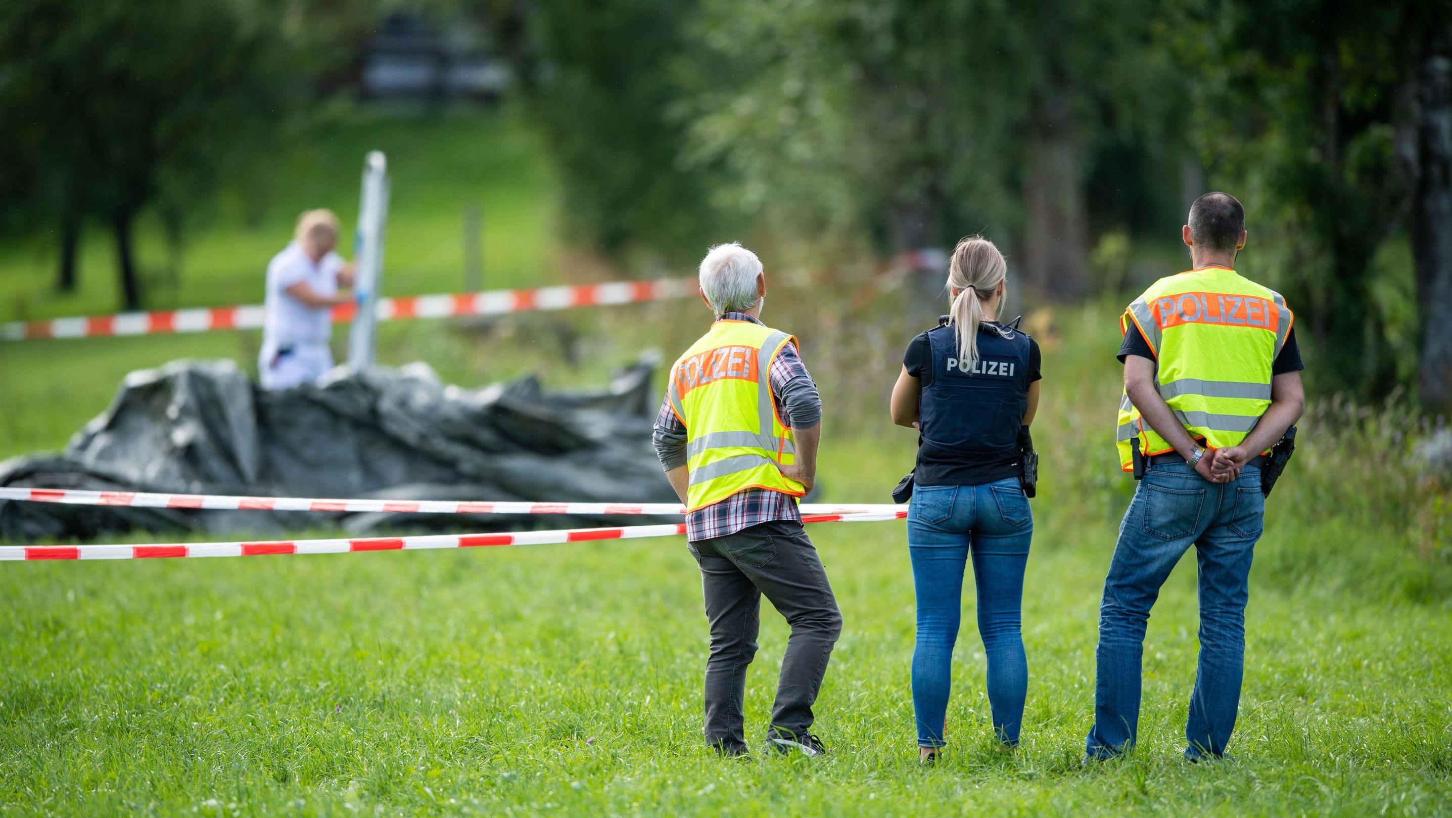 Polizisten stehen an einem abgesperrten Bereich an einem Bachlauf im Kreuther Ortsteil Scharling.