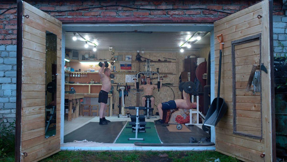 Blick in eine Garage, in der drei Russen an Fitnessgeräten trainieren