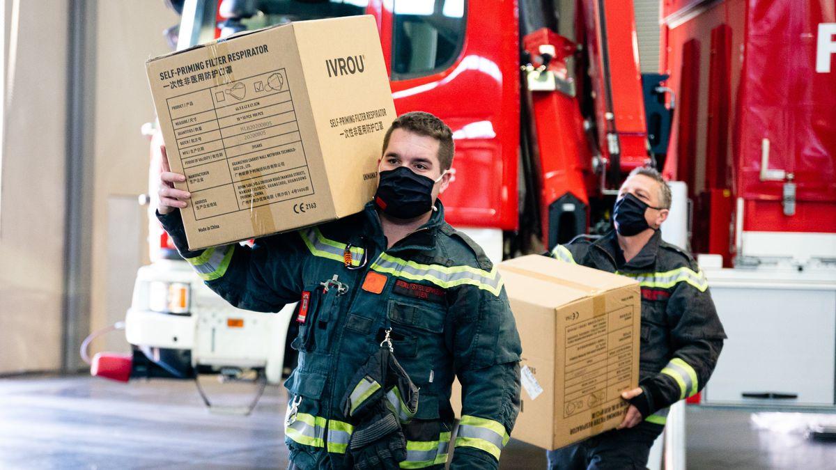 Feuerwehrmänner tragen Kisten auf ihren Schultern