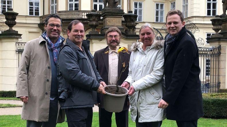 Fünf Personen stehen vor der Deutschen Botschaft in Prag und halten einen Topf mit einem kleinen Baum.