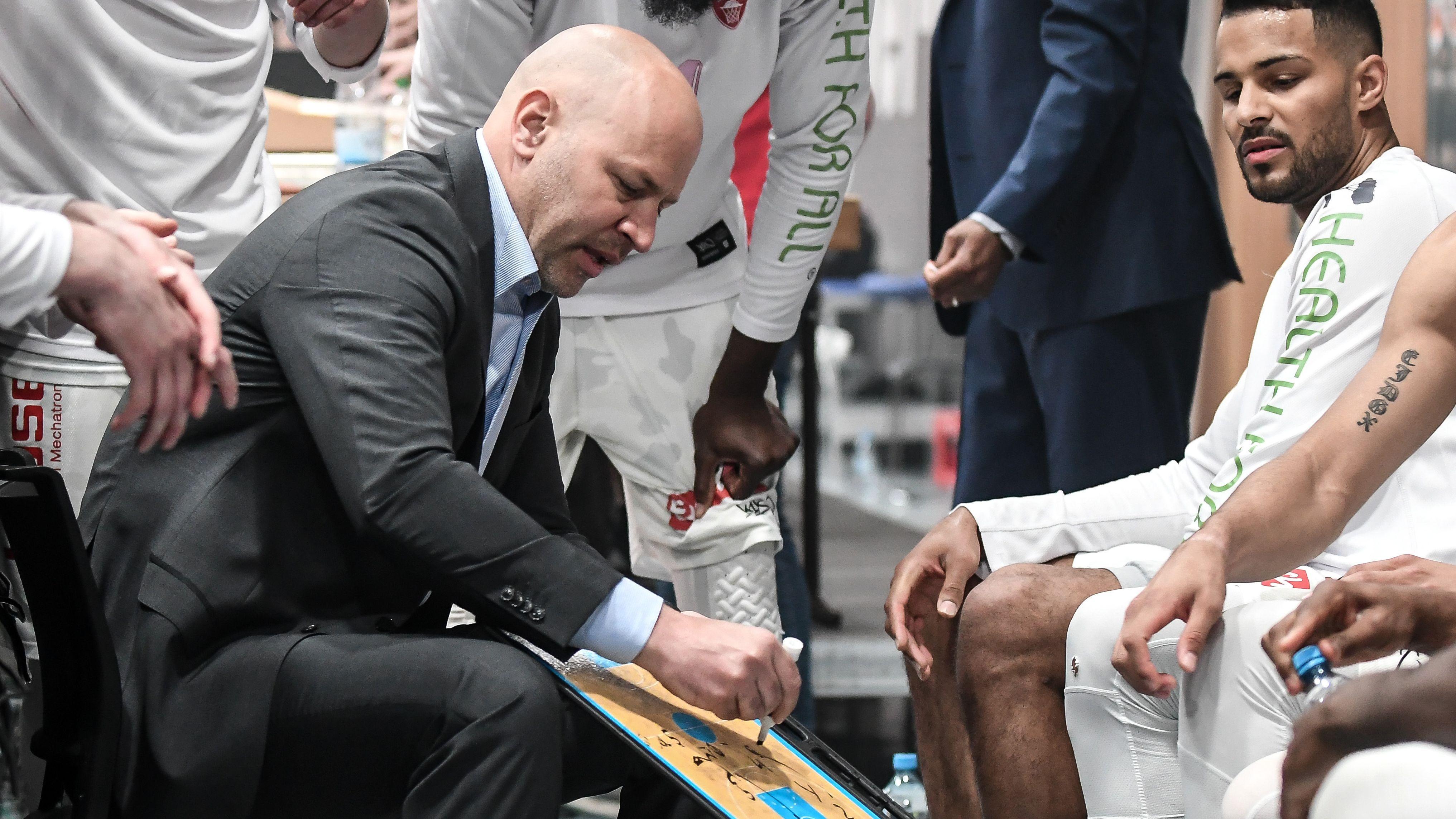 Trainer Denis Wucherer gibt mit einer Schreibtafel taktische Tipps an seine Mannschaft