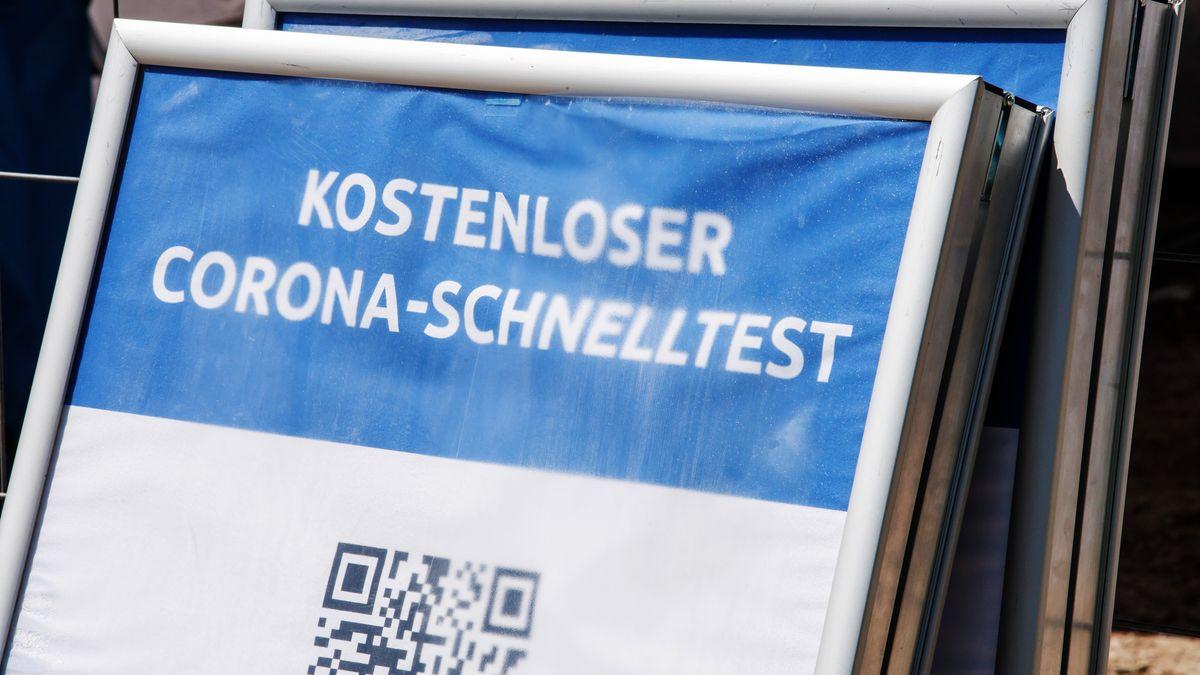 """Symbolbild: Ein Schild mit der Aufschrift """"Kostenloser Corona-Schnelltest"""" steht vor einem Testzentrum."""