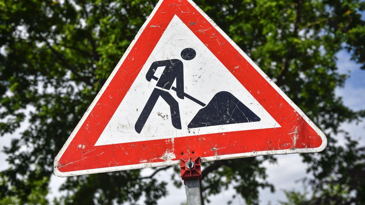 Ein rotes Baustellen-Schild zeigt einen Arbeiter mit Schaufel, im Hintergrund Bäume.