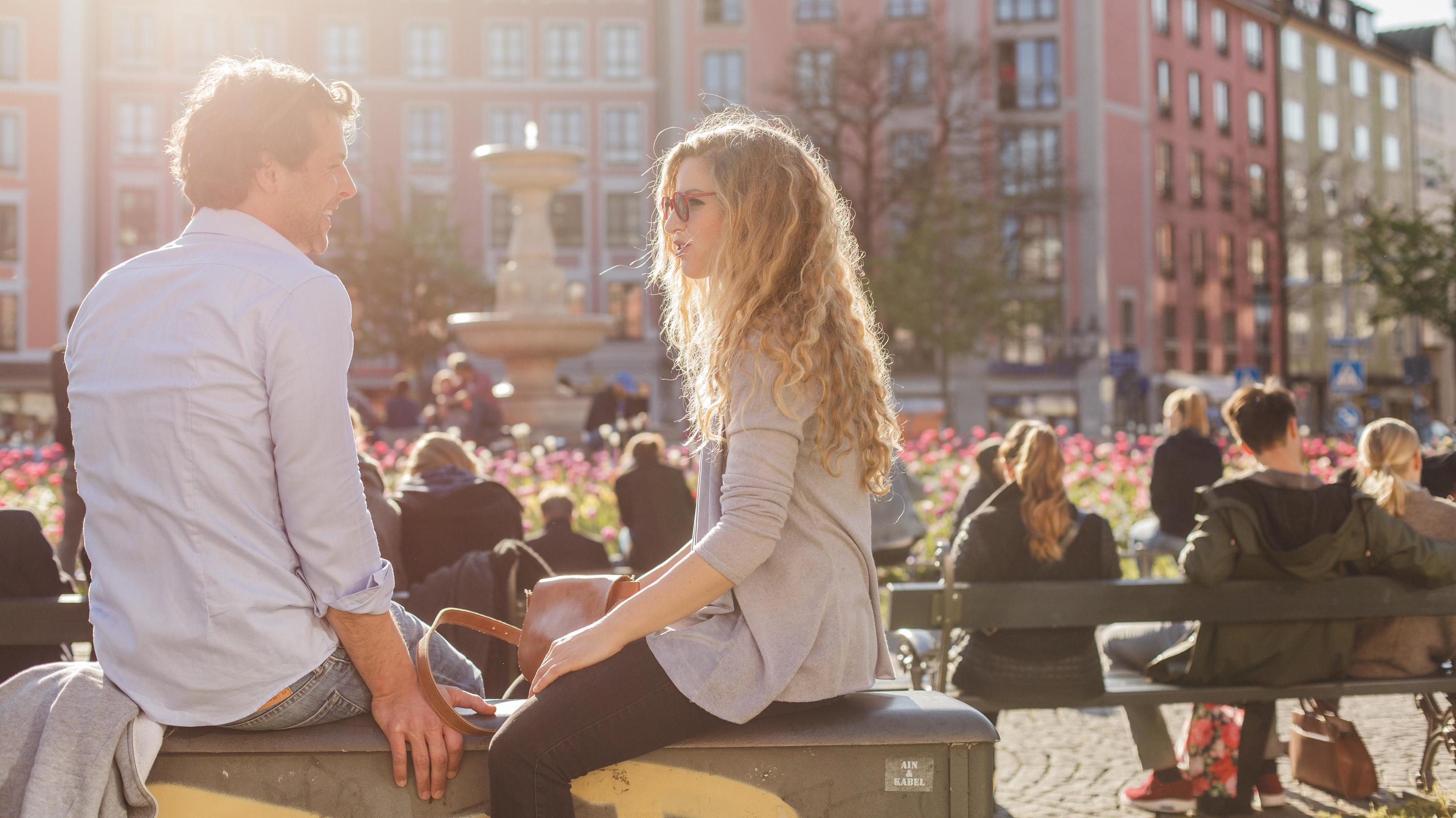 Paare genießen die frühlingshaften Temperaturen am Gärtnerplatz in München.