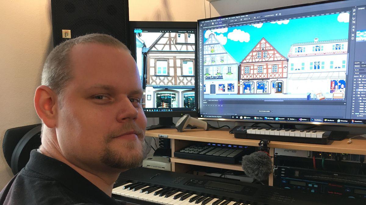 """René Kraus, """"Der Ente"""", sitzt vor einem Bildschirm auf dem sein Forchheim-Computerspiel zu sehen ist."""