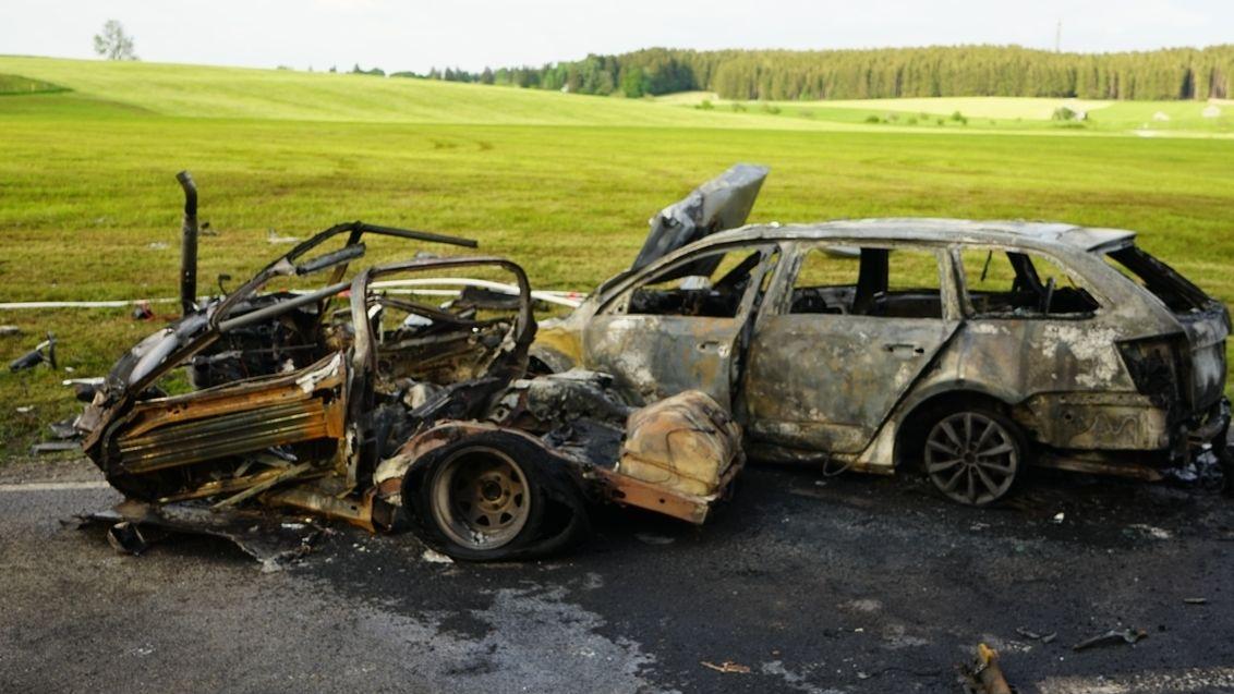 Ausgebrannte Fahrzeugwracks an Straßenrand