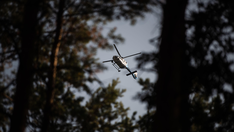 Polizeihubschrauber fliegt über Bäume, Pilot hält Ausschau nach Waldbränden (Symbolbild)