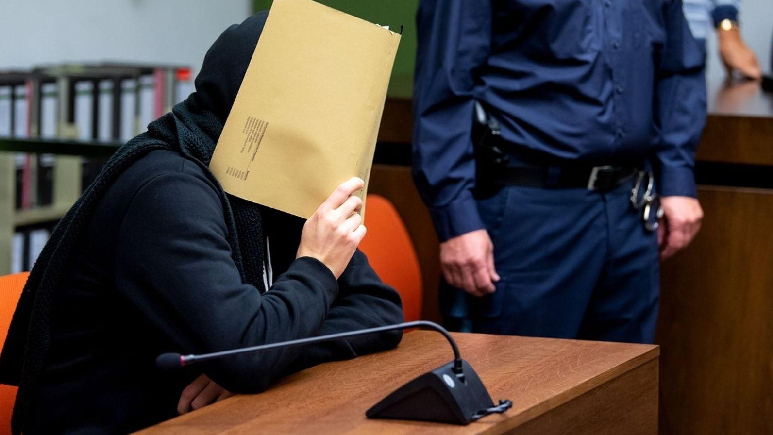 Ein Angeklagter hält eine Mappe vor sein Gesicht.