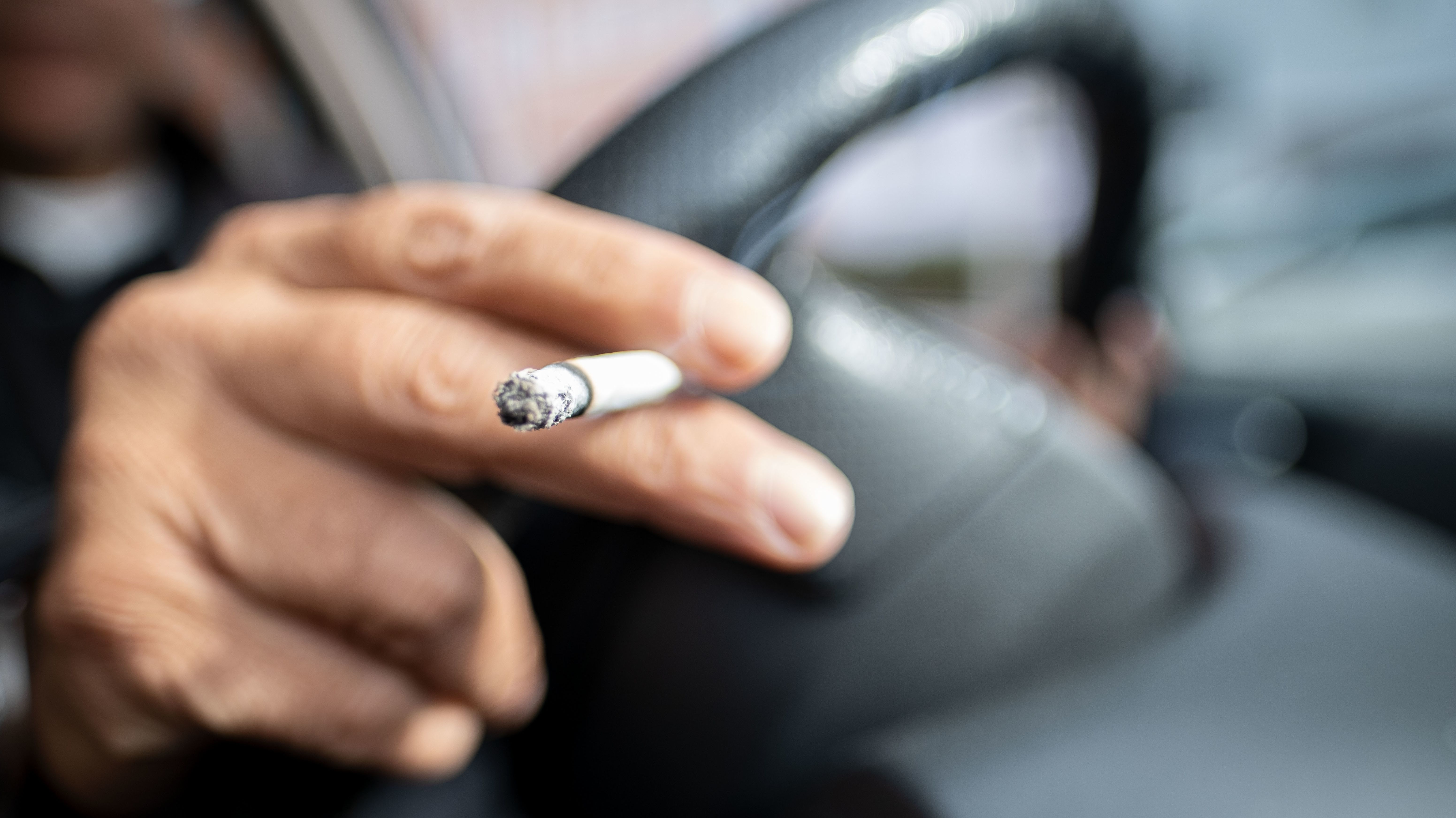 Symbolbild: Ein Mann raucht eine Zigarette im Auto