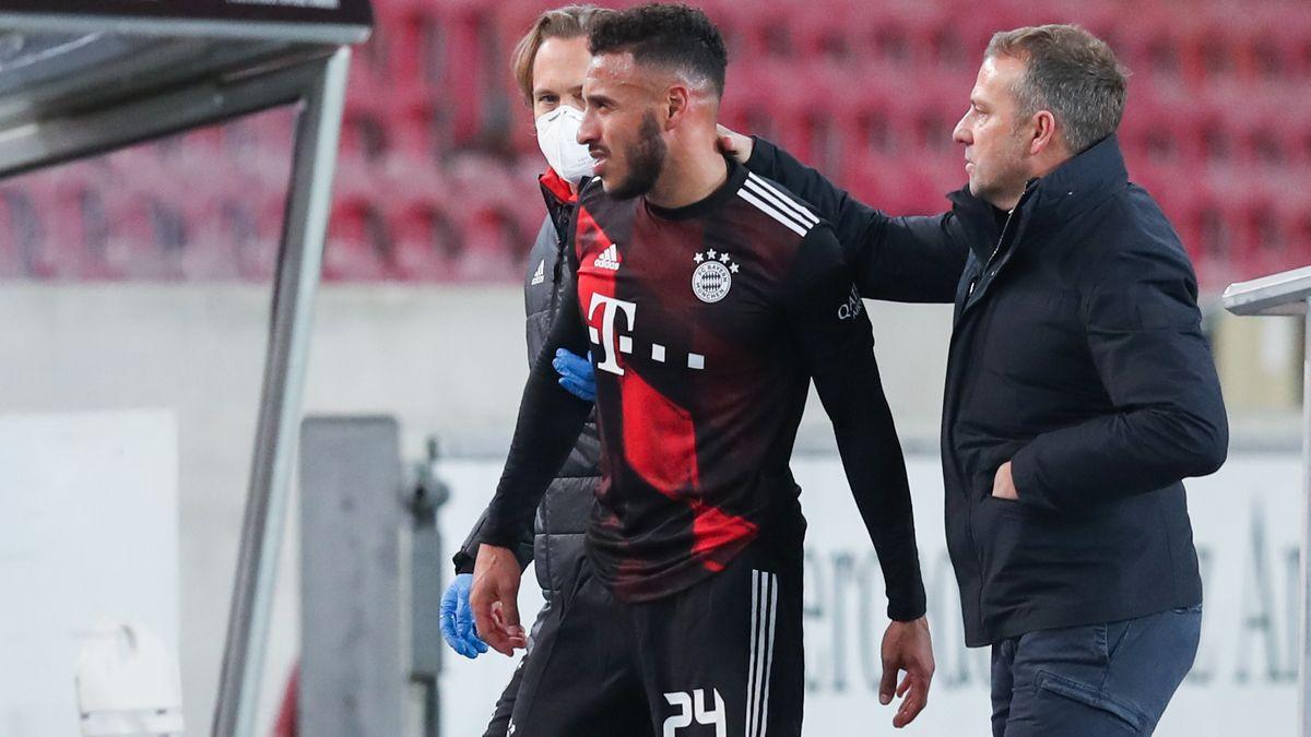 Münchens Corentin Tolisso geht verletzt vom Platz und klatscht mit Münchens Trainer Hansi Flick (r) ab