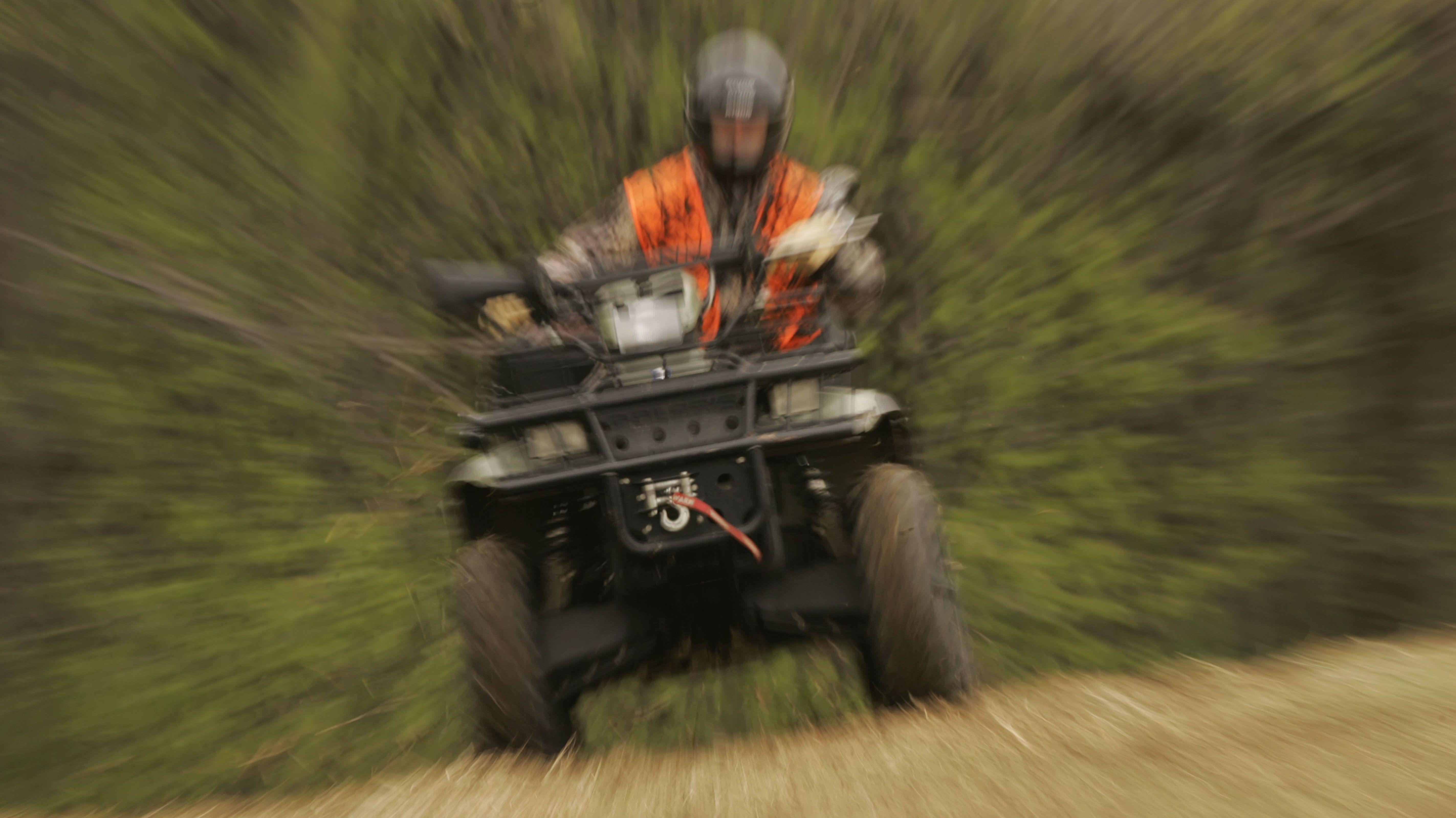 Verzerrtes Bild: Ein Mann mit oranger Warnweste fährt auf einem Quad.