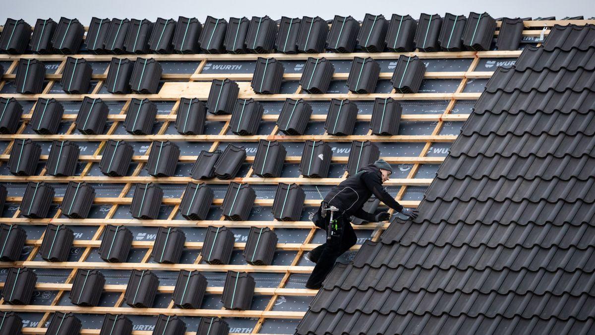 Ein Dachdeckermeister setzt eine Dachpfanne auf der Dachfläche eines Hauses.
