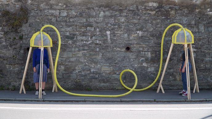 Zwei Frauen stehen jeweils unter einer Plastikabdeckung, die mit einem gelben Schlauch verbunden sind.