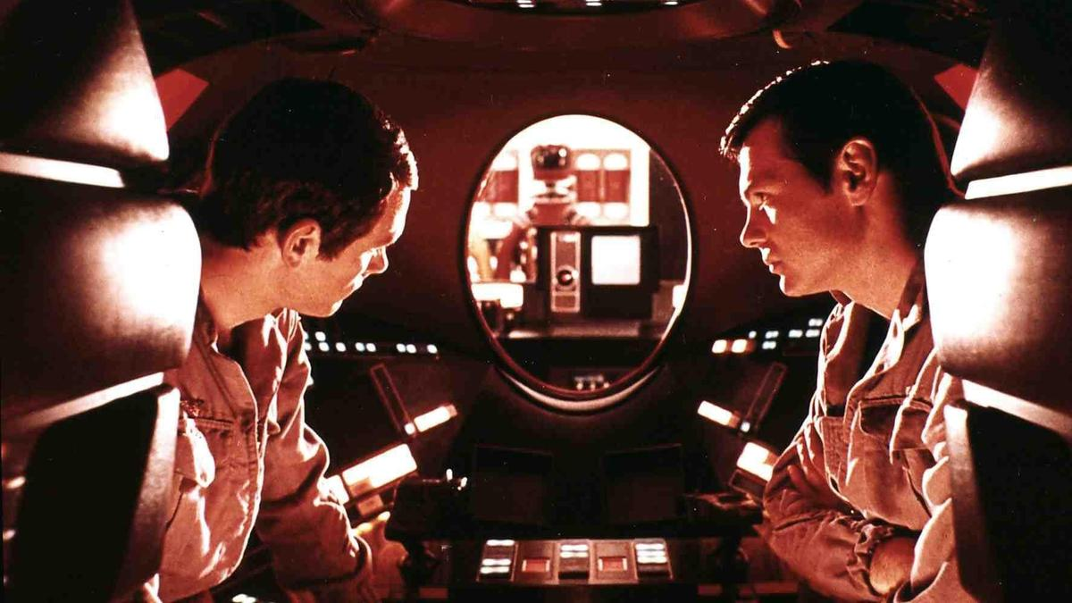 """Die Astronauten David (Keir Dullea, l) und Frank (Gary Lockwood, r) unterhalten sich, im roten LIcht des roten """"Auges"""" des Computers HAL 9000. Filmszene aus """"2001: A Space Odyssey"""""""