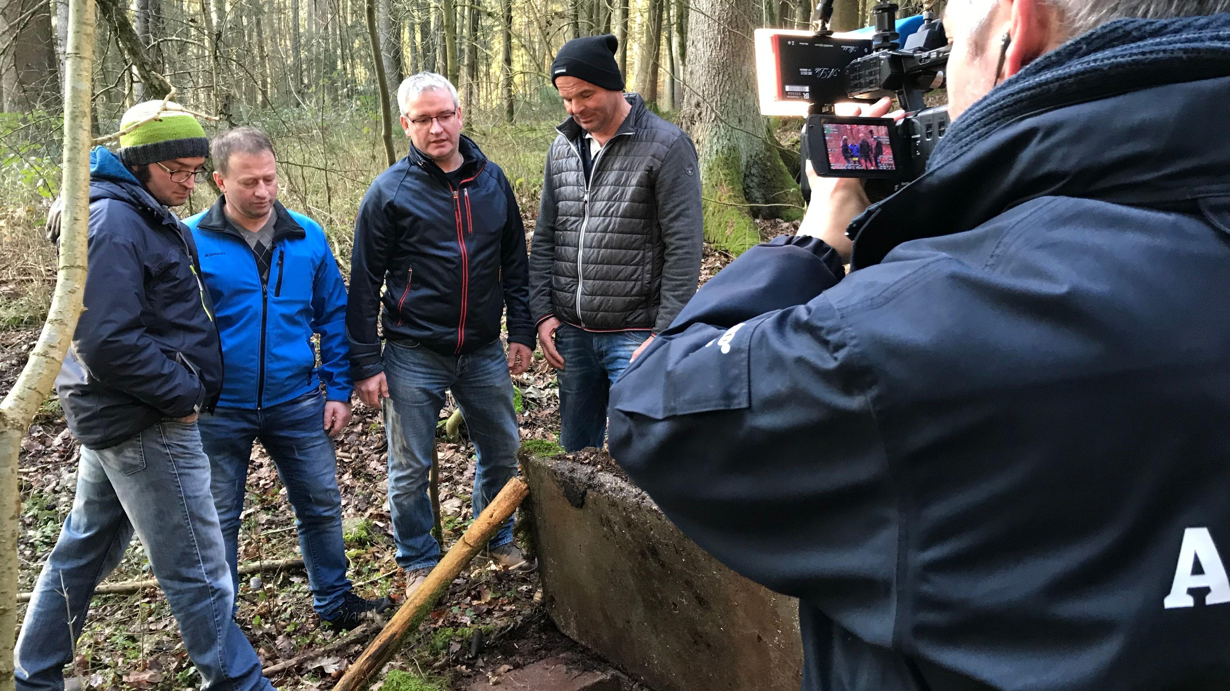 Landwirte begutachten eine Messstelle im Wald.