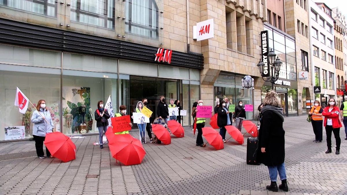 Demonstration mit roten Regenschirmen vor einer Filiale von H&M in Nürnberg