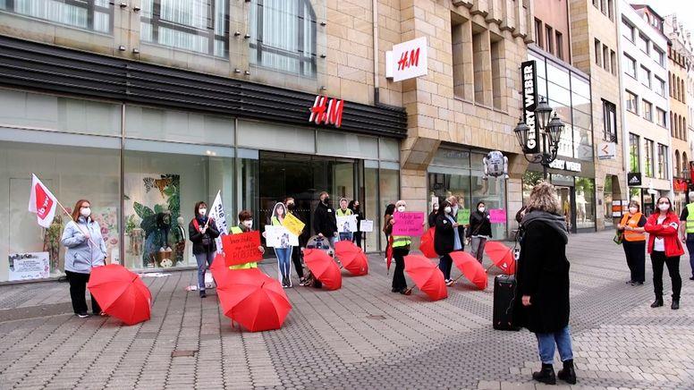 Demonstration mit roten Regenschirmen vor einer Filiale von H&M in Nürnberg | Bild:BR Fernsehen
