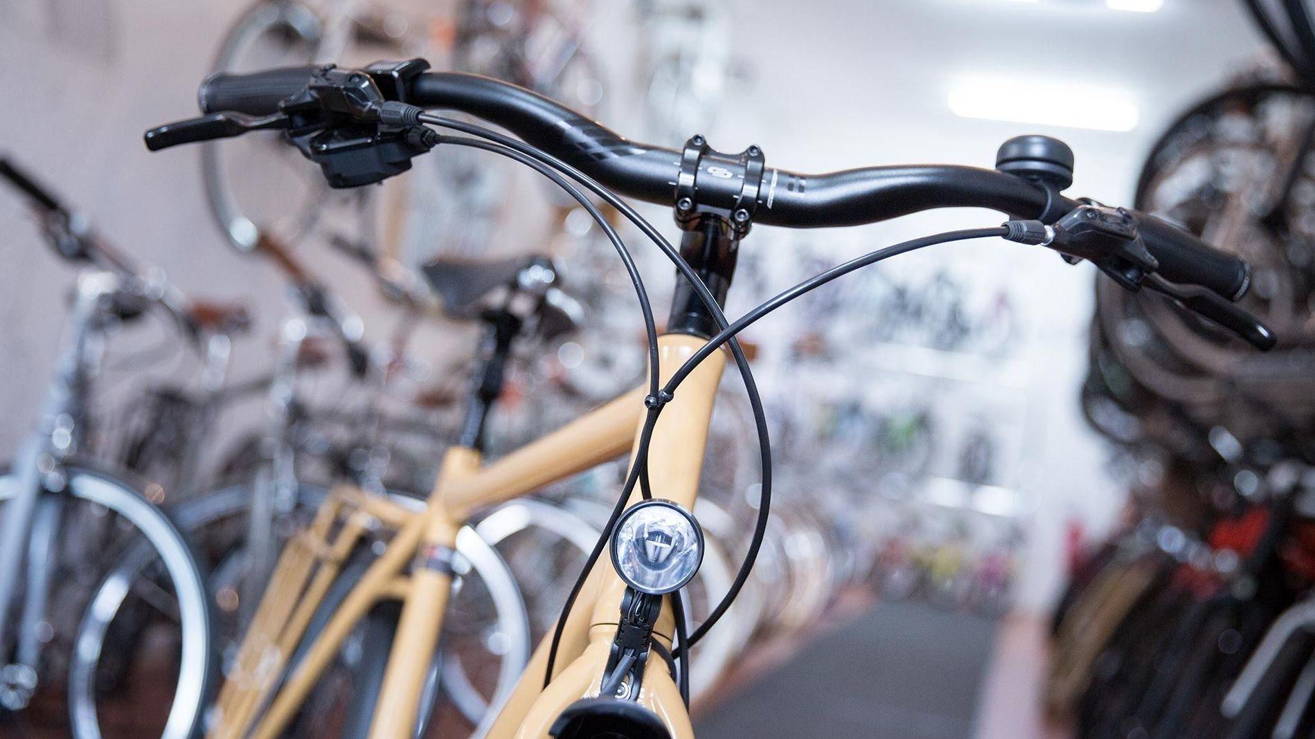 Ein beigefarbenes Fahrrad steht in einem Geschäft, dahinter viele andere Fahrräder.
