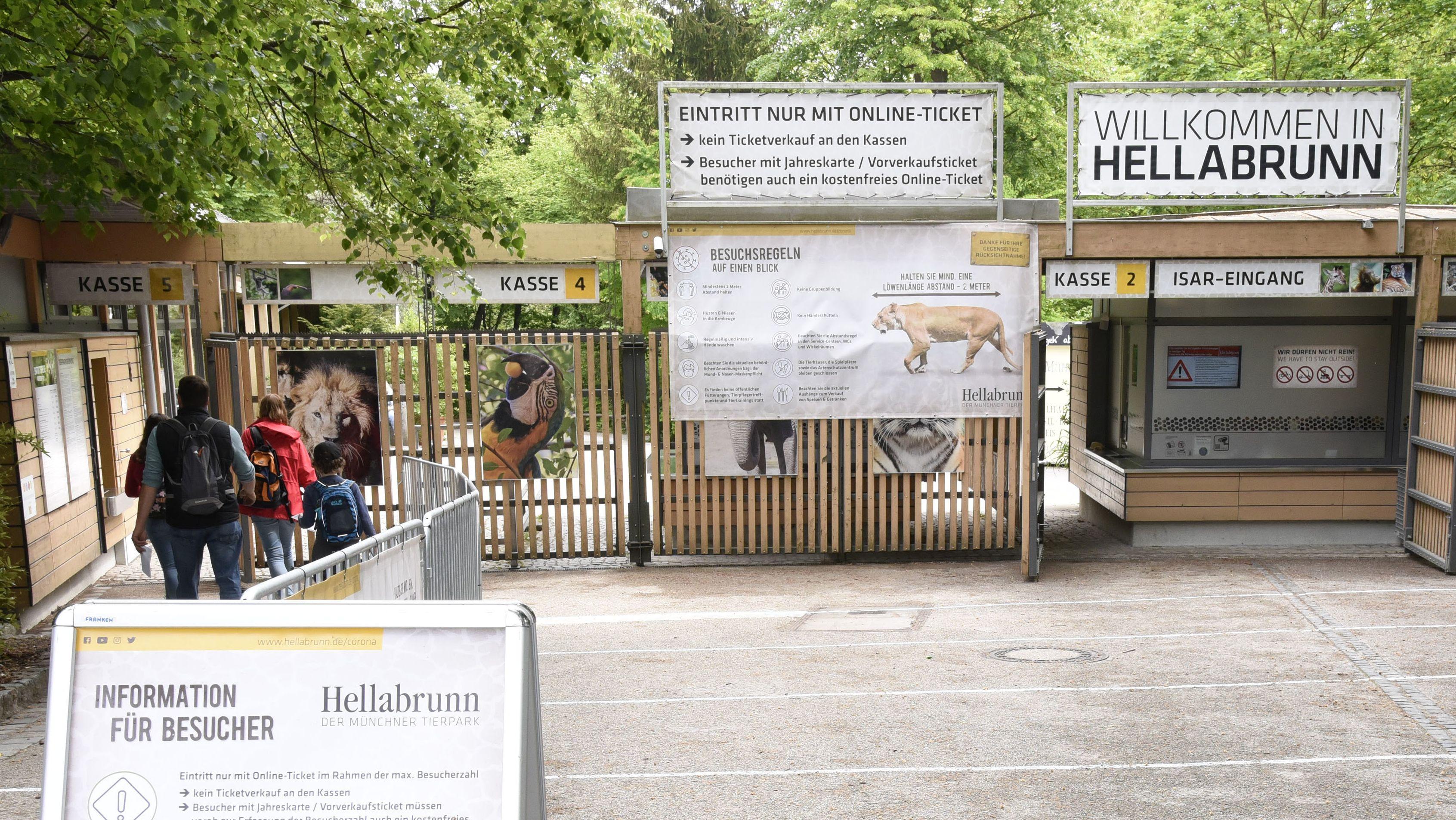 Am Isar-Eingang des Münchner Tierparks Hellabrunn hängen Tafeln und Plakate, die über die Besuchsregeln informieren und darauf, dass der Eintritt nur mit einem vorher gekauften Online-Ticket möglich ist.