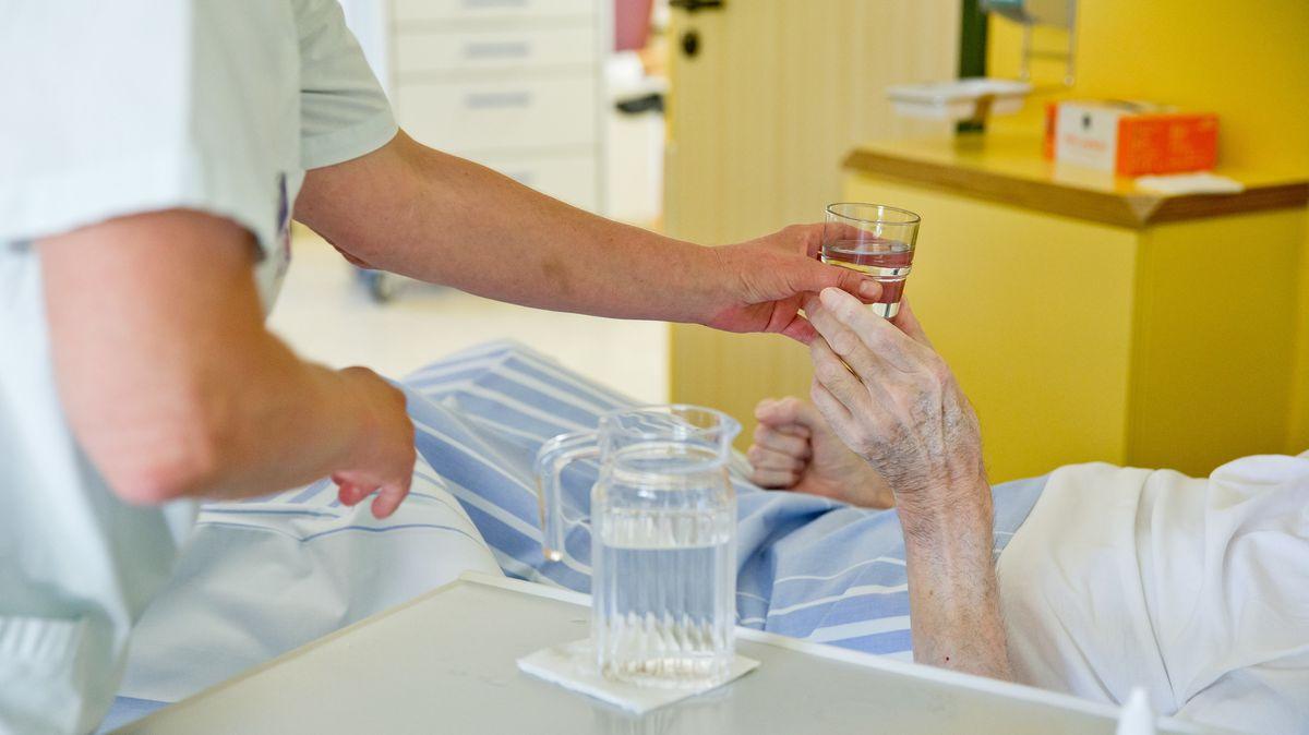 Ein Pfleger hilft einer Seniorin