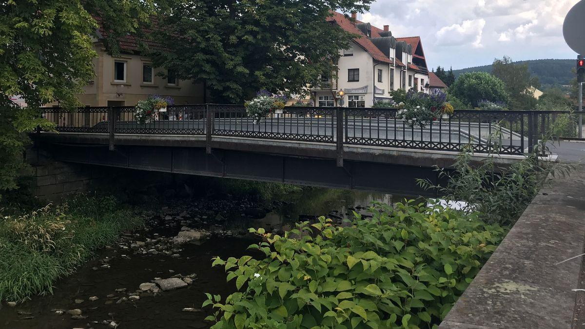 Die Spitalbrücke in der Kronacher Innenstadt führt über die Kronach, die wenig Wasser führt, im Hintergrund eine Häuserzeile.