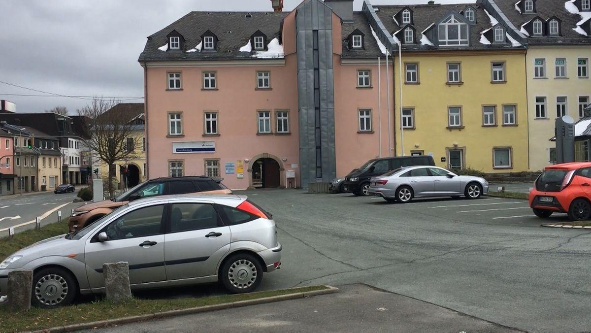 Auf einem Parkplatz stehen Autos, dahinter Häuser.