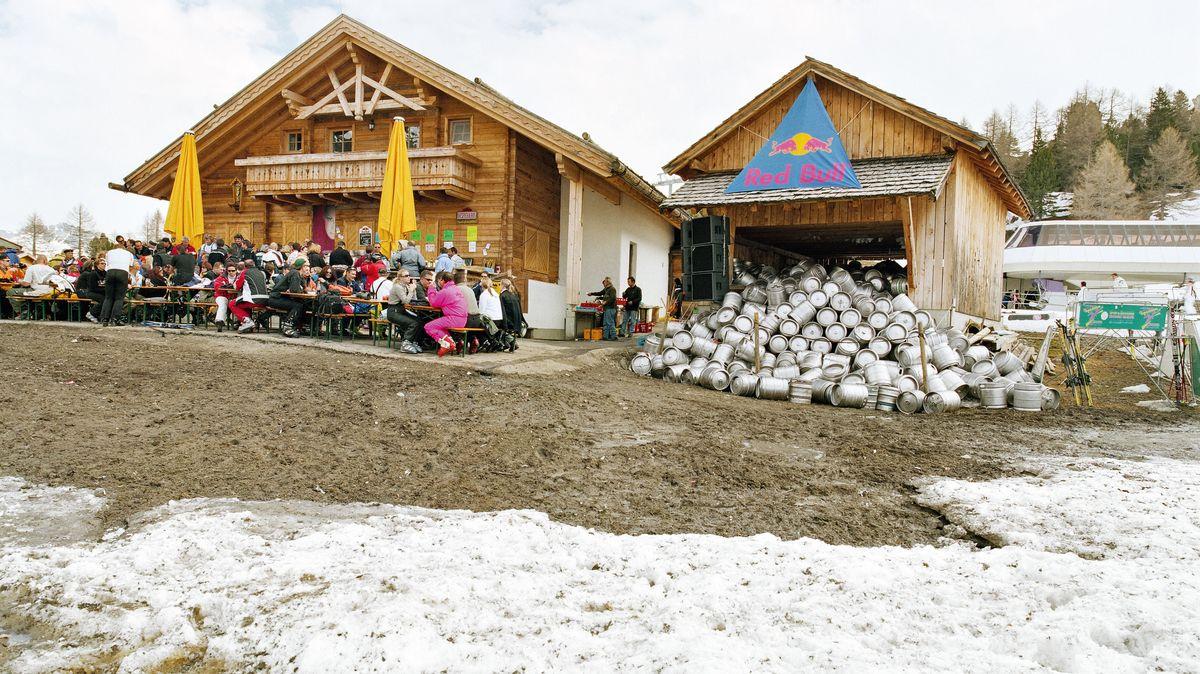 Links sitzen Skifahrer im Biergarten vor einer Alpenhütte mit Holzfassade und gelben Sonnenschirmen, rechts eine Hütte mit Red-Bull-Werbebanner, vor der sich Aluminiumfässer stapeln.