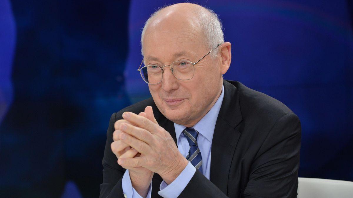 Journalist sitzt mit gefalteten Händen am Tisch