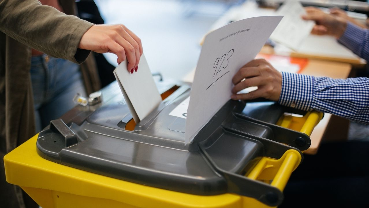 Stimmzettel werden in eine Wahlurne geworfen.