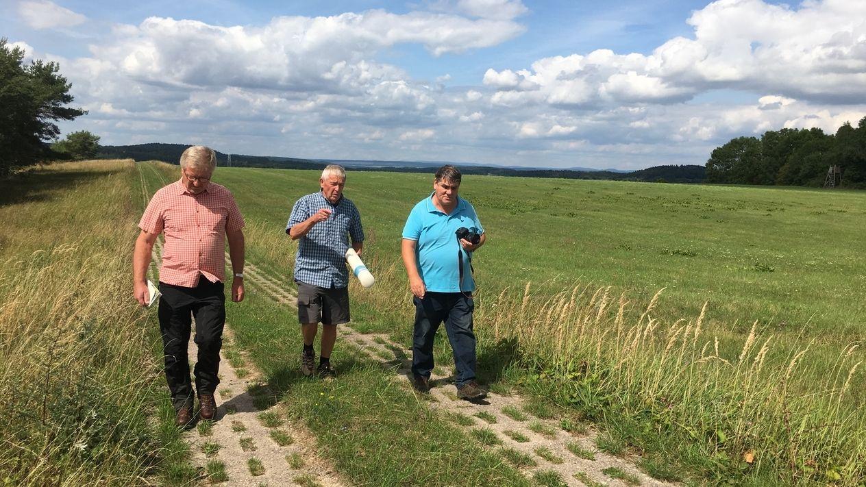 Drei Männer wandern auf dem ehemaligen Grenzstreifen der DDR.