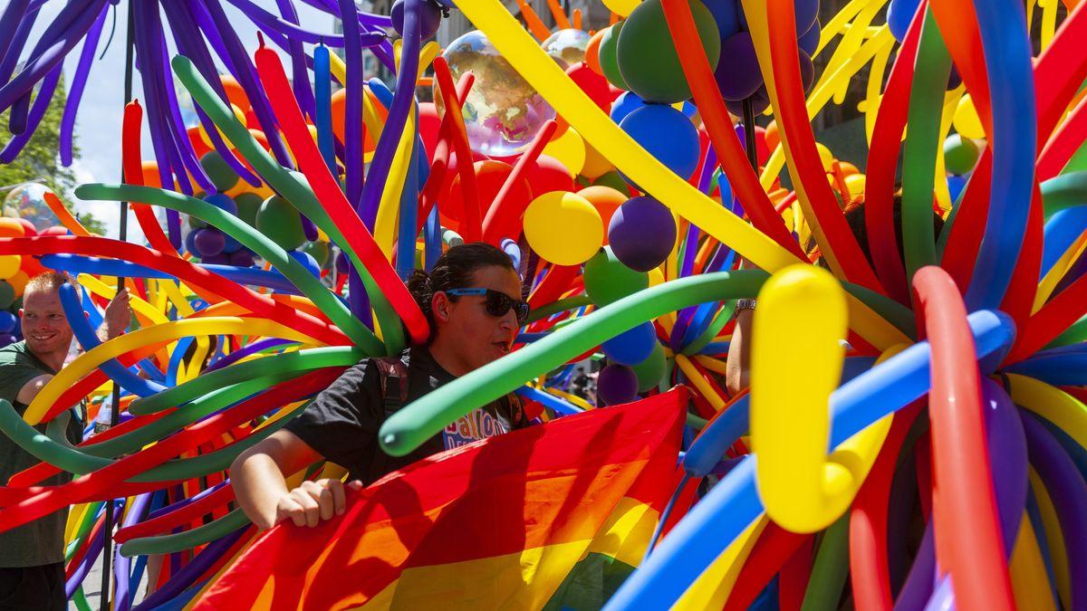 Viele bunte Luftballons bei der Gay Pride Parade in New York. Dazwischen eine Person mit dunkler Sonnenbrille