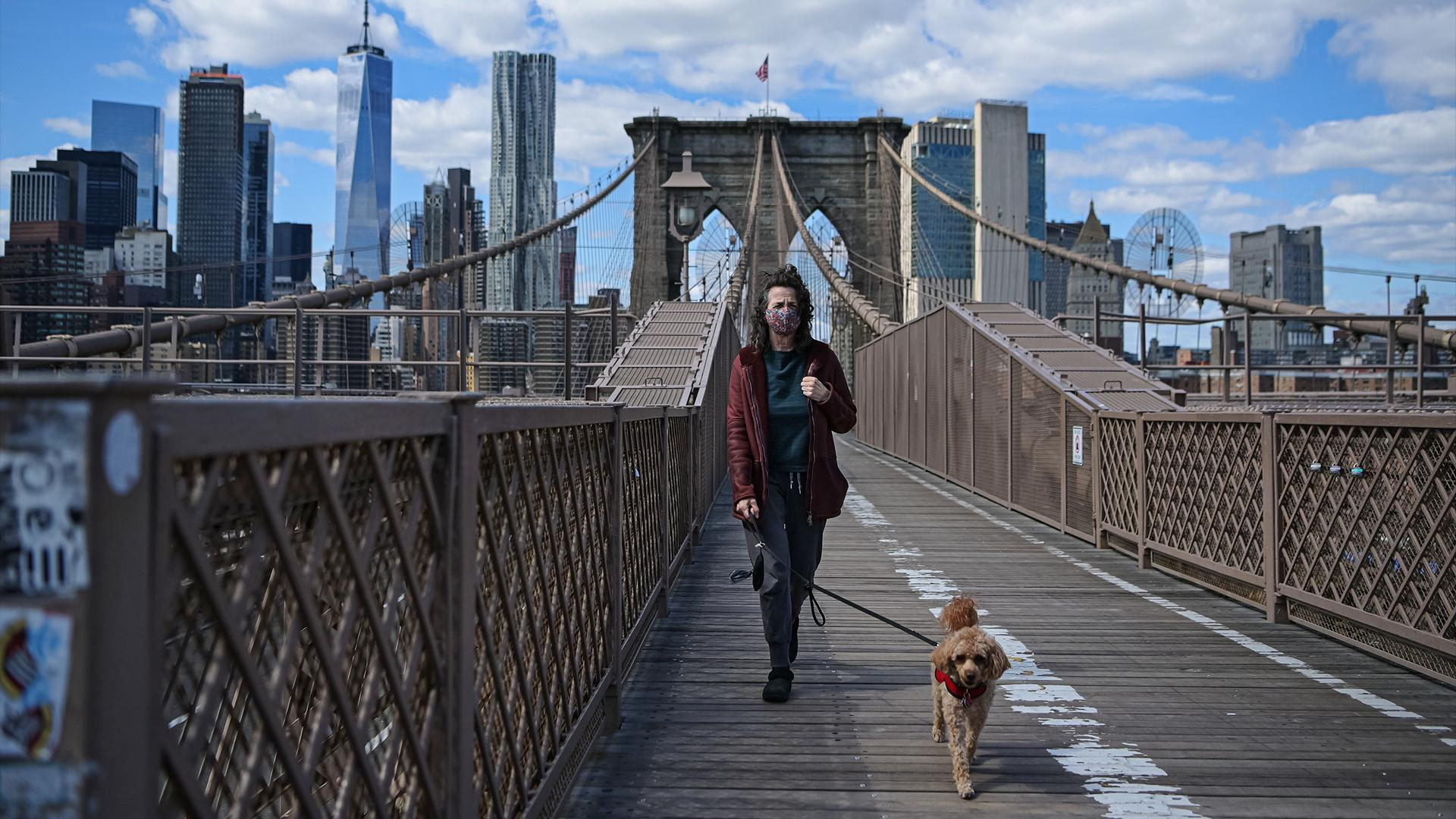 Eine Frau trägt eine Maske, während sie mit ihrem Hund über die Brooklyn Bridge geht