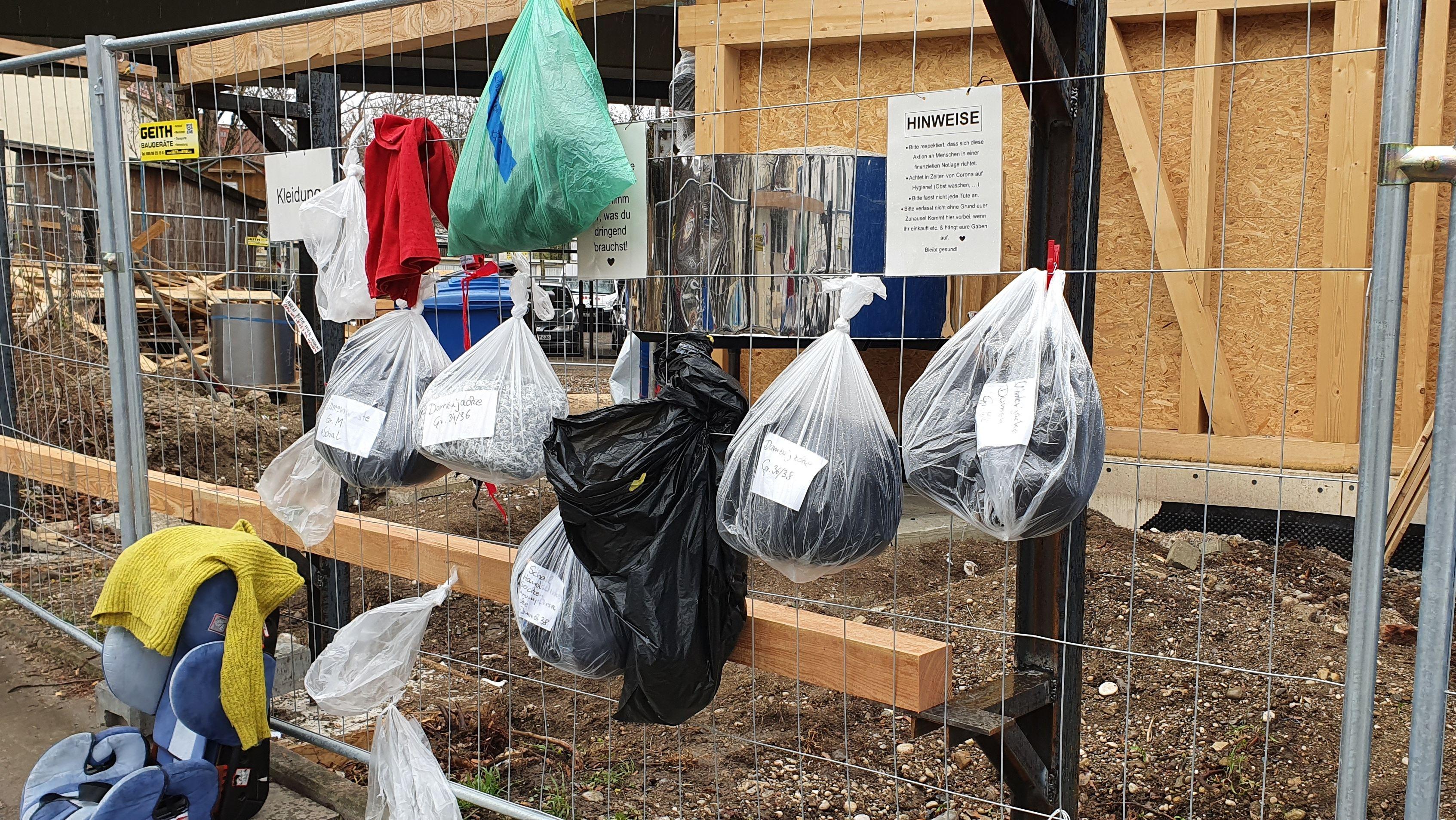 An einem Bauzaun hängen durchsichtige Plastiksäckchen mit Spenden.