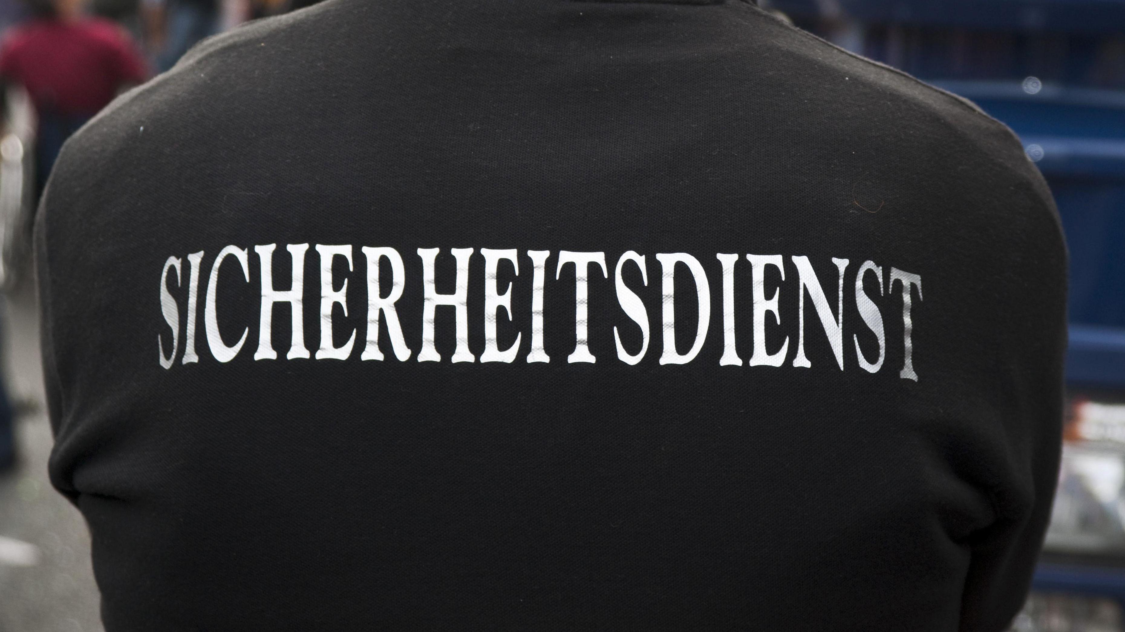 """""""Sicherheitsdienst"""" steht auf dem Rücken eines Mannes."""