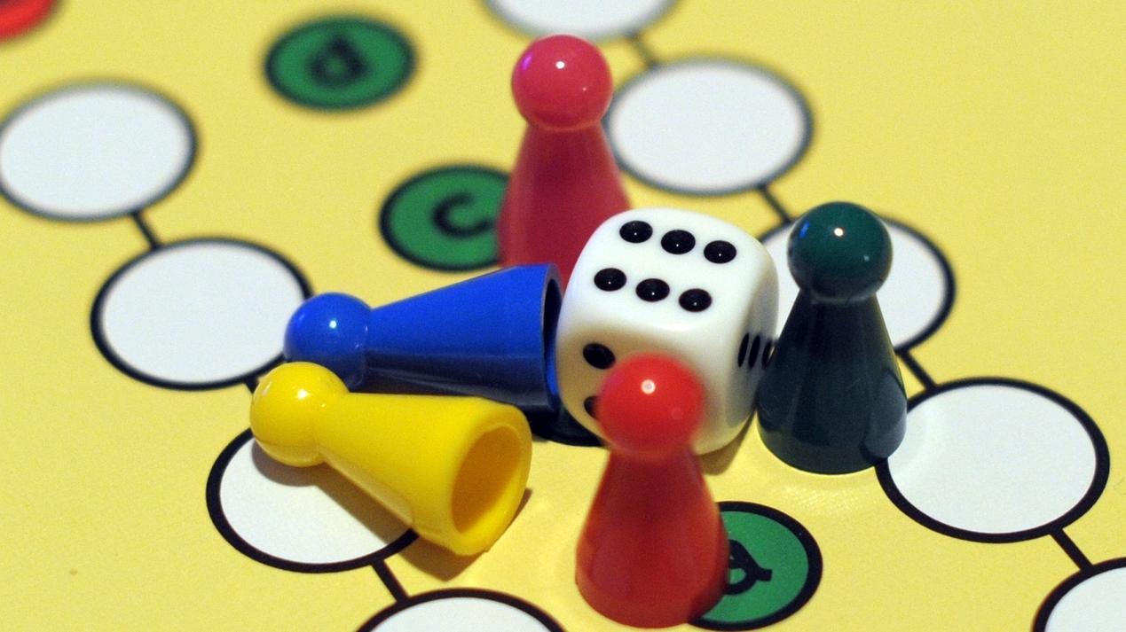 Spielfiguren und ein Würfel auf einem Mensch-ärgere-dich-nicht Spielbrett