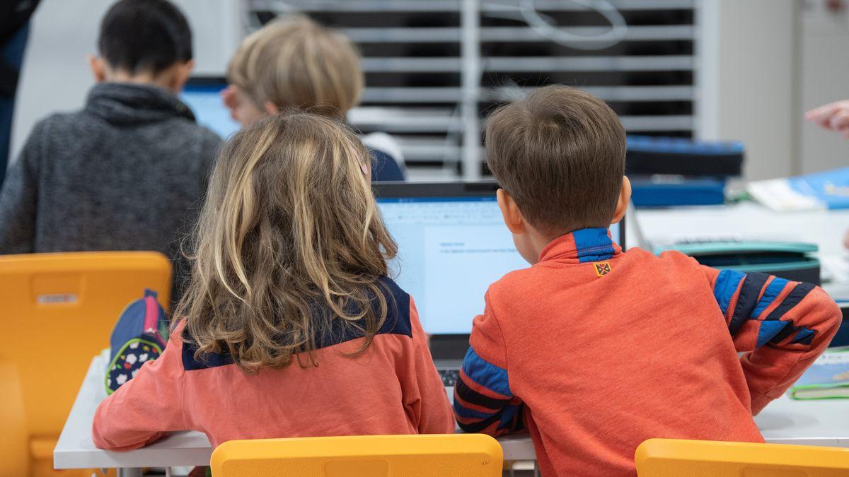 Schüler einer dritten Klasse sitzen vor dem Laptop
