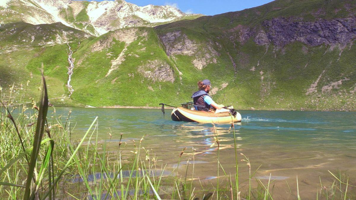 Mann in Paddelboot auf Bergsee