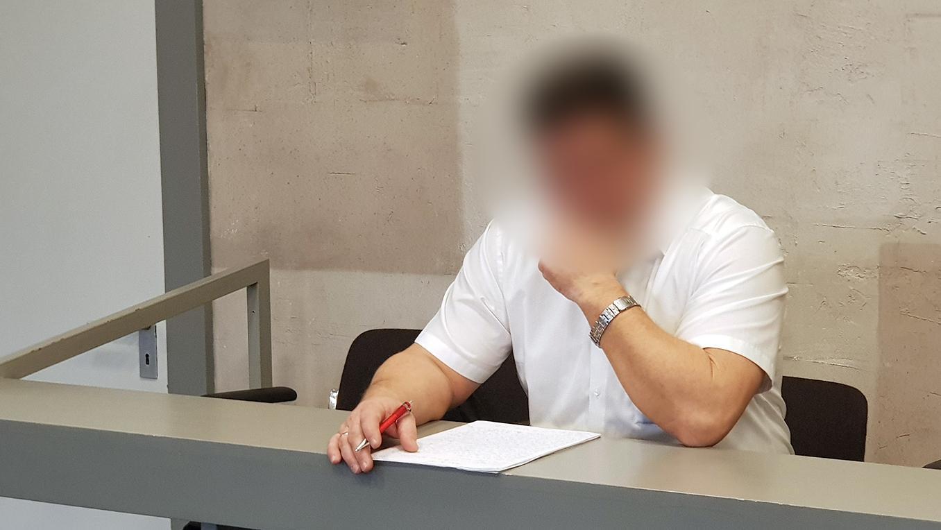 Polizist sitzt im Gerichtssaal an einem Tisch, vor sich seine Unterlagen