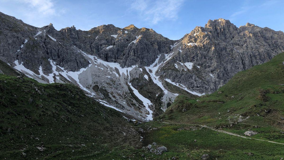 Grüne Hügel vor schneebedeckter Alpenkulisse im Allgäu: Der Weg zur Fiderepass-Hütte.