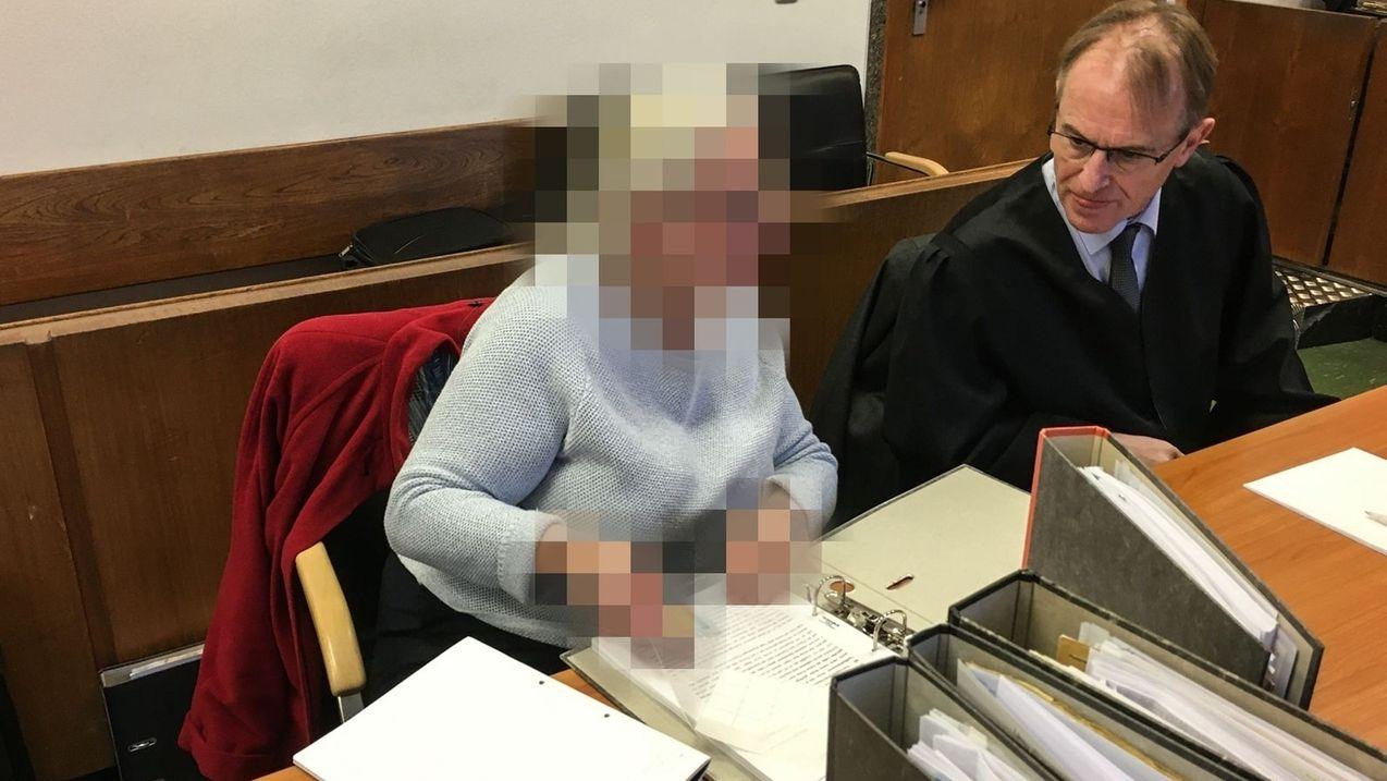 In einem Gerichtssaal sitzen eine verpixelte Frau und ihr Anwalt