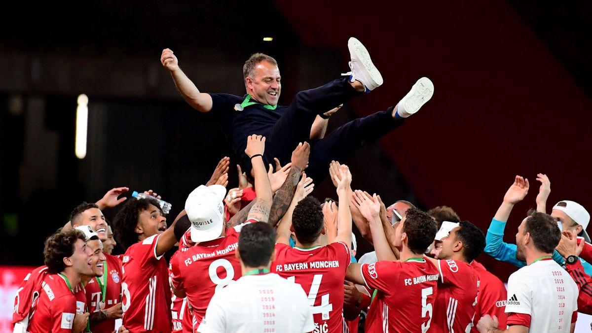 Münchens Trainer Hansi Flick (M) wird von seinen Spielern in die Luft geworfen.