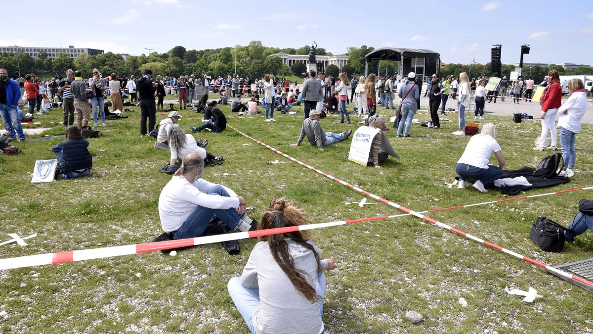 Menschen stehen und sitzen mit Abstand zueinander auf der Münchner Theresenwiese