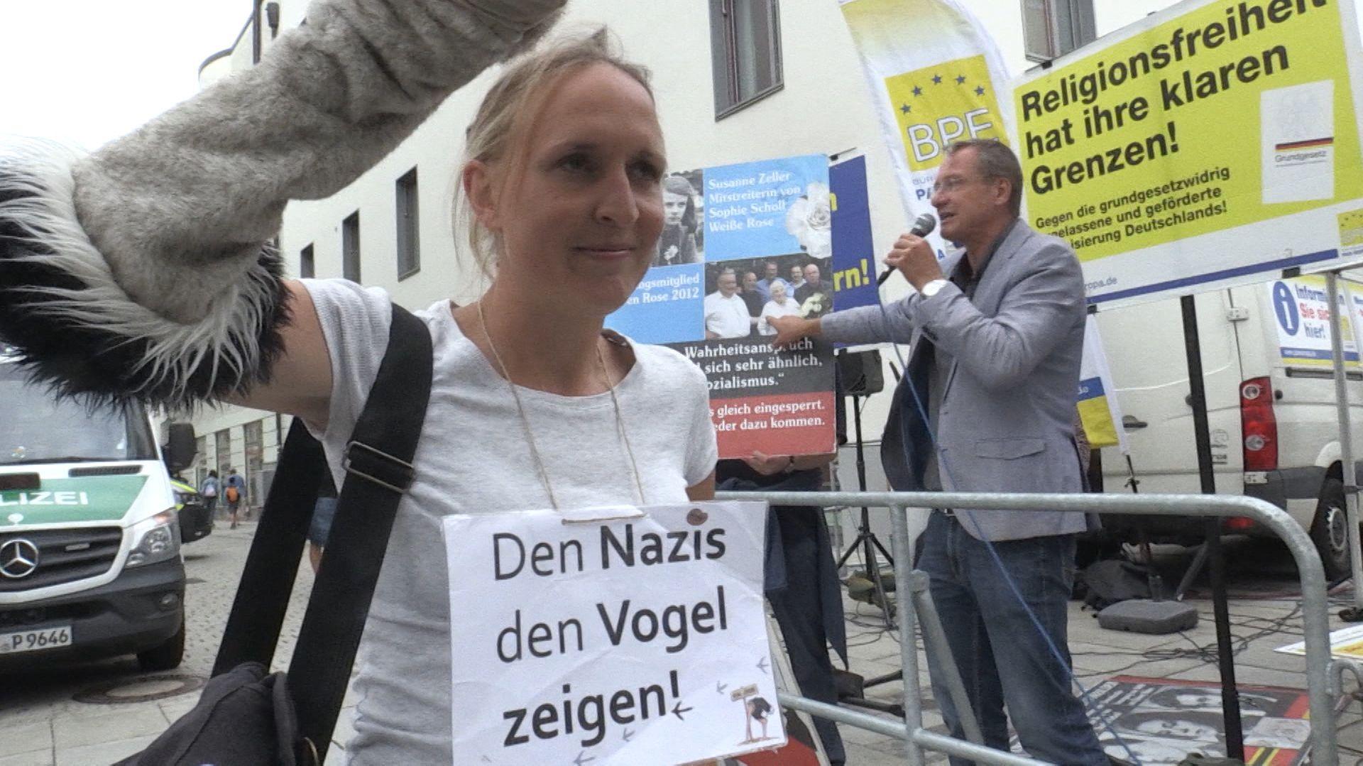 Eine Gegendemonstrantin zeigt dem Islamkritiker Michael Stürzenberger ihren Protest.