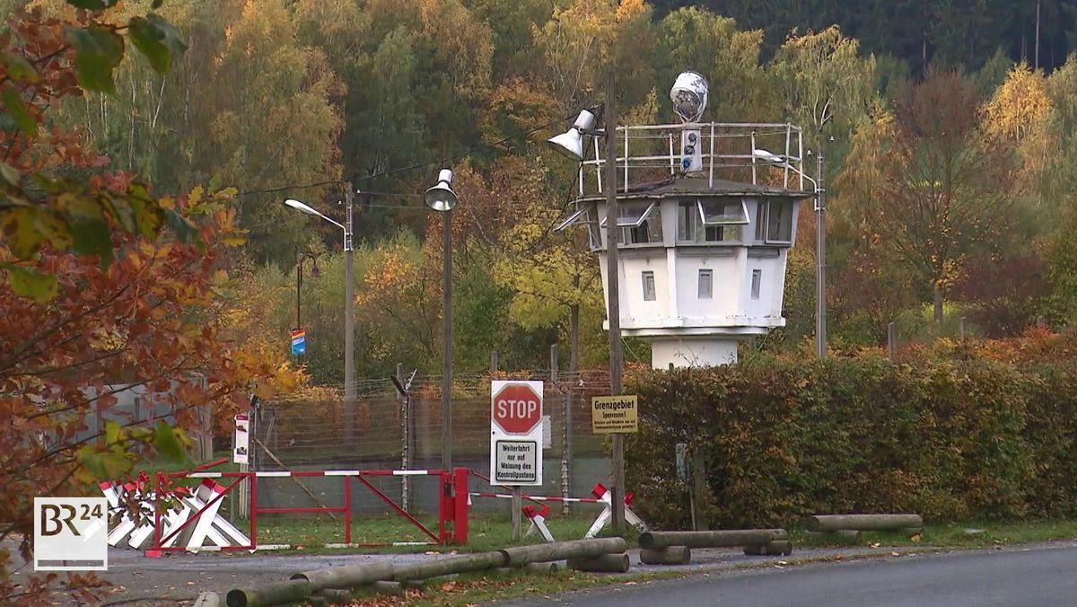 Ein Original-Grenzturm in Mödlareuth aus der Zeit vor der deutsch-deutschen Wiedervereinigung, davor ein Stacheldrahtzaun und rot-weiße Absperrungen.