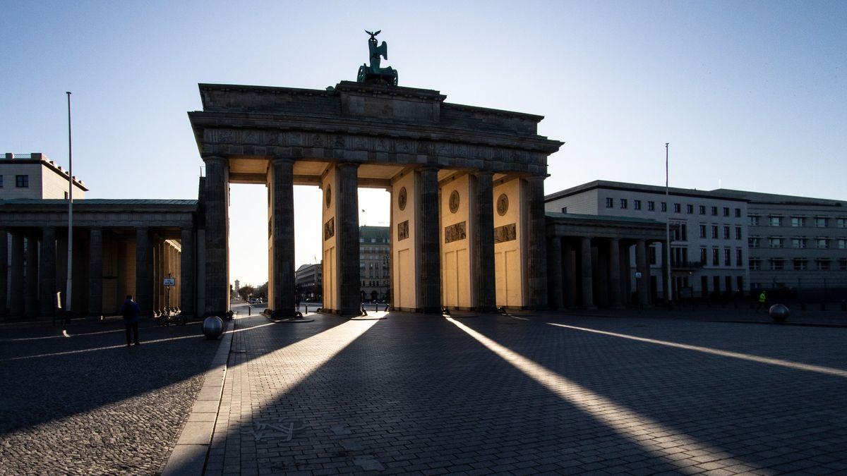 Im Licht der aufgehenden Sonne ist das Brandenburger Tor als Silhouette zu erkennen.