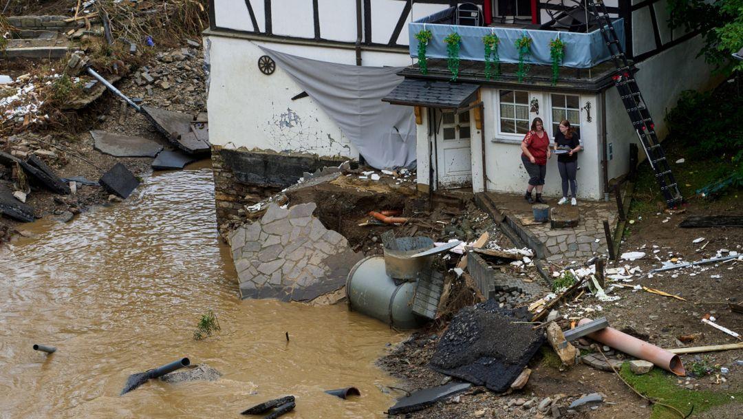 Rheinland-Pfalz, Schuld: Zwei Frauen stehen neben Trümmern vor einem Haus in dem Ort im Kreis Ahrweiler am Tag nach dem Unwetter mit Hochwasser.